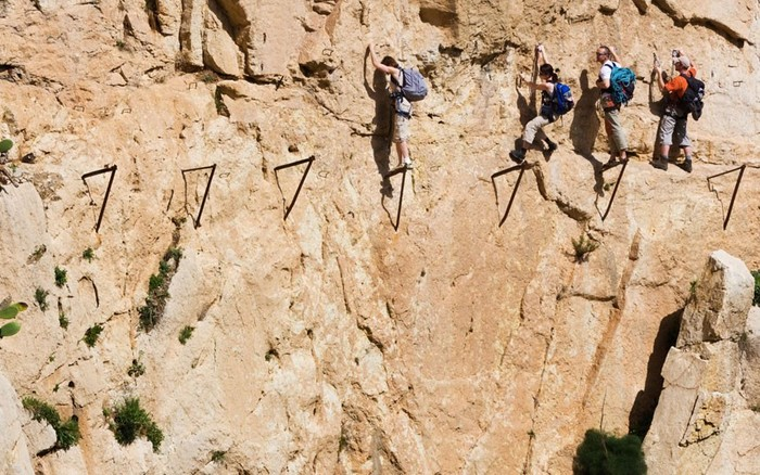AXRBDK Climbers traverse the now broken Camino del Rey at El Chorro gorge near Alora Malaga Province Spain